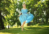 Young charming laughing woman in beautiful dress jumps on meadow — Stock Photo