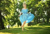 美しいドレスの若い魅力的な笑い女性草原にジャンプします。 — ストック写真