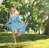 молодая женщина в голубом платье, перепрыгивая через зеленая трава — Стоковое фото