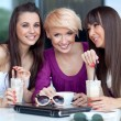 Three young women having coffee break — Stock Photo