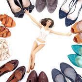Mujer de belleza en lencería entre muchos pares de zapatos — Foto de Stock