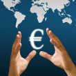 Hand hold Euro icon with world map background - Stock Photo