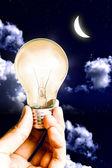 Ciepłe żarówka w ręku świecić światło księżyca i niebo — Zdjęcie stockowe