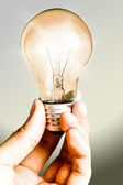 Clear light Bulb shining in the hand — Stock Photo