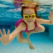 图库照片: Girl smiles, swimming under water in pool