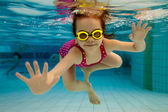 A garota sorri, nadar debaixo de água na piscina — Foto Stock