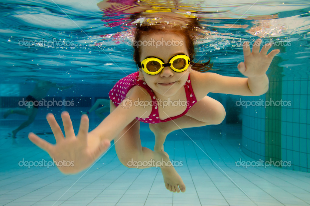 The little girl in the water park swimming underwater and smiling — Stock Photo #5588990