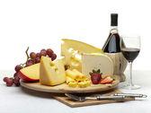 Bodegón de queso en una bandeja redonda de madera — Foto de Stock