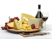 Cheese still life on a wooden round tray — 图库照片