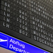 Departure board at airport - Stock Photo