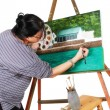 Female artist painting a picture - Stock Photo