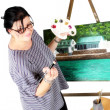 Stock Photo: Female artist smiling with painting in background