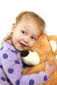 Little girl hugging a teddy bear — Stock Photo