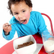 Little boy eating breakfast cereal — Stock Photo