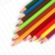 Pencil crayons on white writing paper — Stock Photo