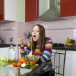 Woman eating salad in the kitchen — Stock Photo