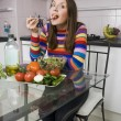 Woman eating salad on the kitchen — Stock Photo