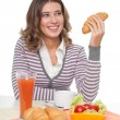 Happy woman with croissant — Stock Photo