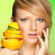 Face of beautiful woman with pyramid of fruits — Stock Photo
