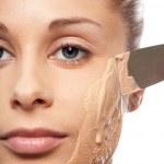 Put on makeup foundation with spatula — Stock Photo