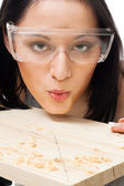 Woman carpenter blow away scobs — Stock Photo