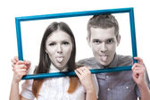 Couple look from frame with stick out tongue — Stock Photo