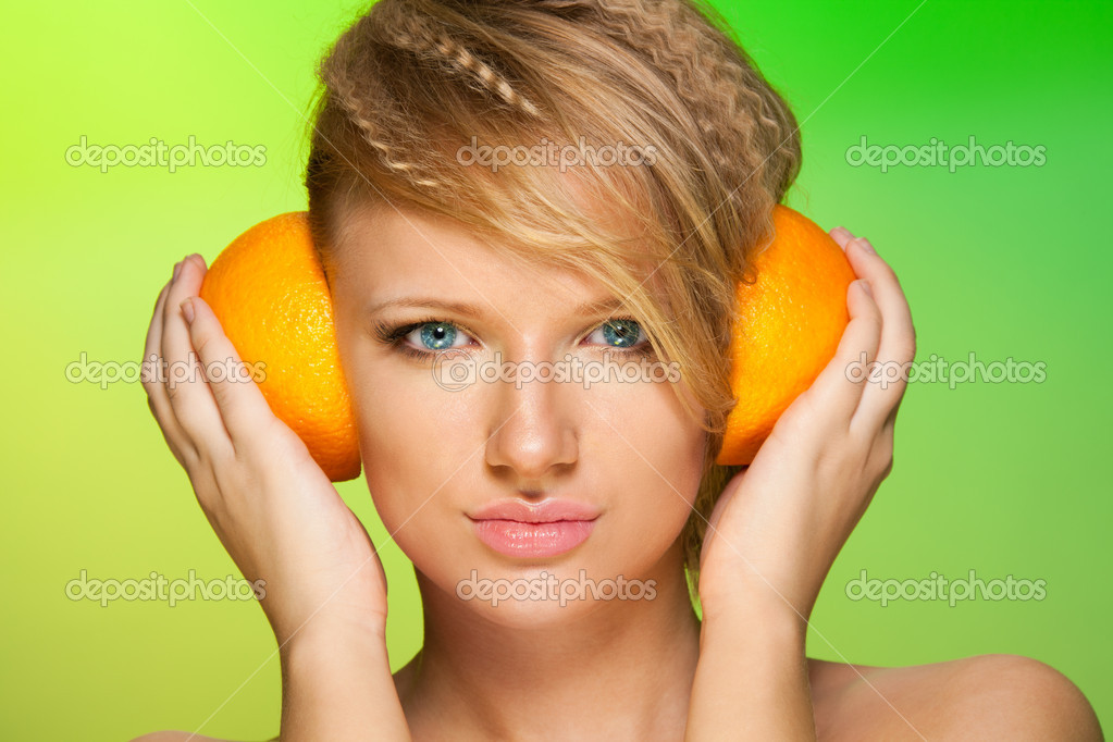 Woman using fruits as a head phones holding halves of oranges — Stock Photo #5558777