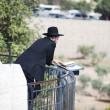 Orthodox Jewish man parrying in front of cemetery in Jerusalem - Stock Photo