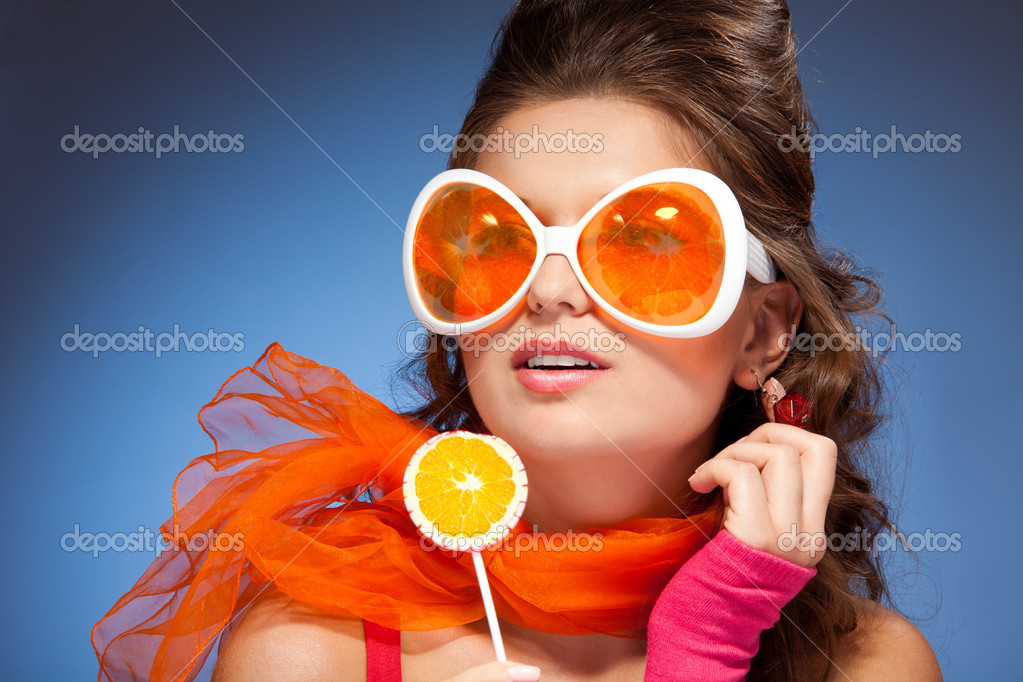 Girl licking lollipop, wearing red scarf with big orange glasses  Stock Photo #5858579