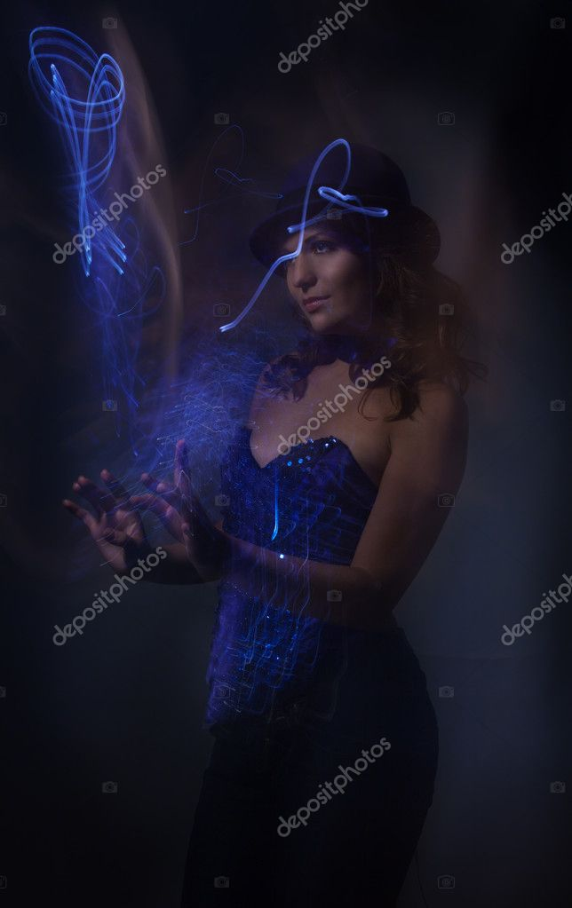 Beautiful woman and blue magic light in her hands  - shoot made with combination of contagious and flash lights — Stock Photo #5858583