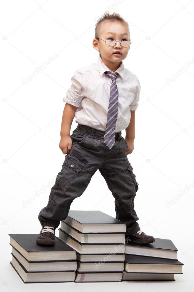 A little Chinese kid with a bossy behavior standing on pile of books  Stock Photo #5858649