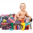Happy baby in basket with clothes — Stockfoto