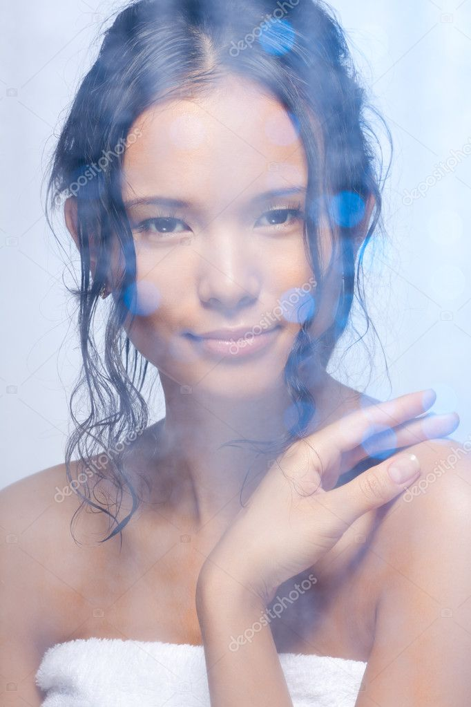 Nice Asian woman in the bathroom behind the frosted glass with wet curly hair — Stock Photo #6288220