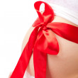 Pregnant woman belly with red bow — Stock Photo