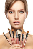 Beautiful woman holding makeup brushes set — Stock Photo