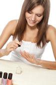 Beautiful woman polishing nails — Stock Photo