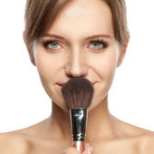 Beautiful woman holding makeup brush — Stock Photo