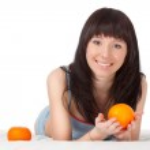 Woman on bed holding orange — Stock Photo #5772308