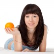 Woman on bed holding orange — Stock Photo #5772324