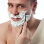 Attractive man shaving his face — Stock Photo
