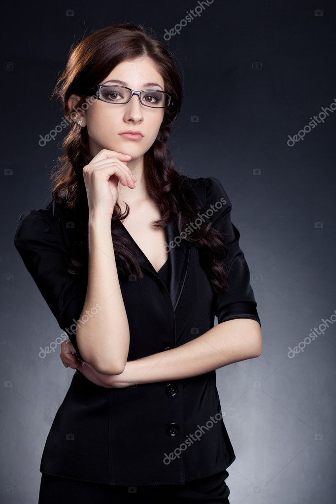 Beautiful businesswoman  wearing glasses posing over black background — Stock Photo #6089177