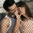 Couple standing near lattice — Stock Photo