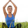 Woman on filed in lotus pose — Stock Photo