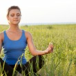 Stock Photo: Woman on filed in lotus pose