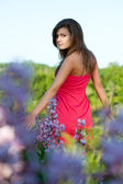 Woman walking trhough the flowers — Stock Photo