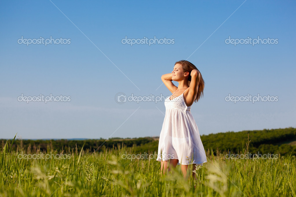 Beautiful happy woman standing on green field over blue skies — Stock Photo #6721134