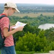 Boy with binoculars and backpack looks at the map on a hike — Stock Photo