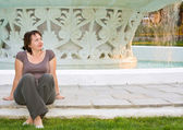 Yang beautiful woman relaxes in front of fountain — Stock fotografie