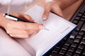 Hand writes a pen on an notebook — Stock Photo