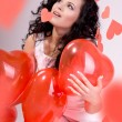 Stock Photo: Womwith red heart balloon on white background